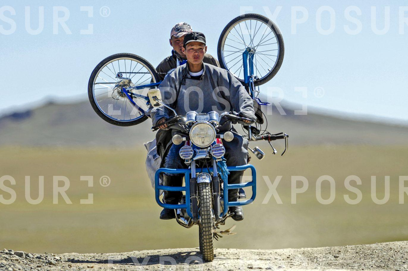 Mongolian boys carrying a bicycle on their motorcycle